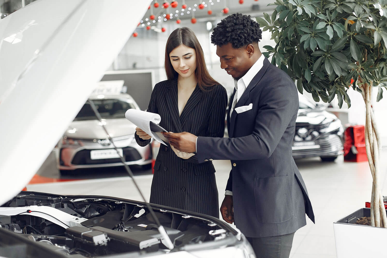 A car salesman reading documents with a consumer