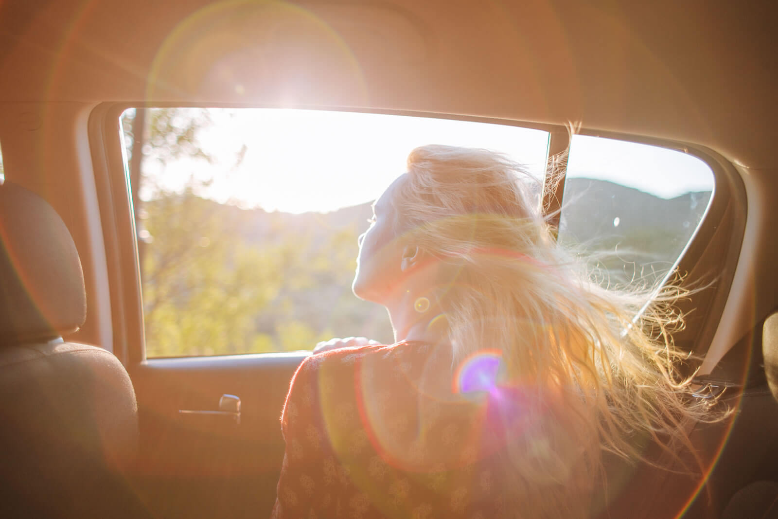 A woman illuminated by sunlight through a  car window